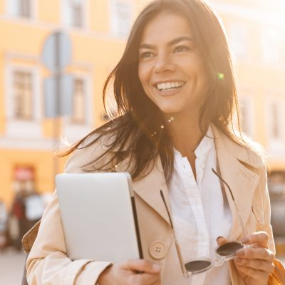 Happy brunette woman in jacket holding laptop computer and looking away outdoors
