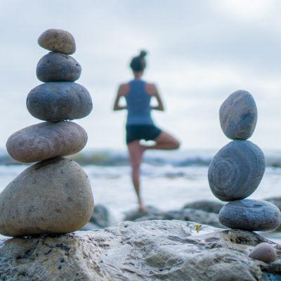 Beautiful girl tree pose yoga by the ocean with stacking rocks