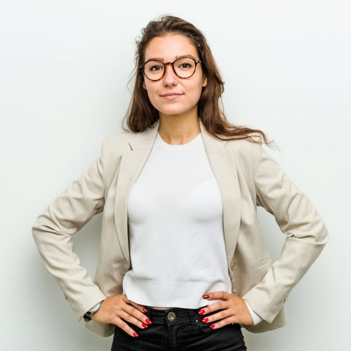 Young european business woman confident keeping hands on her hips.