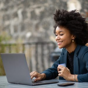 Portrait african american businesswoman sitting outside with laptop computer