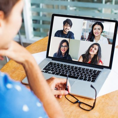 Remote teamwork concept: man talking to his Indian colleagues on video call